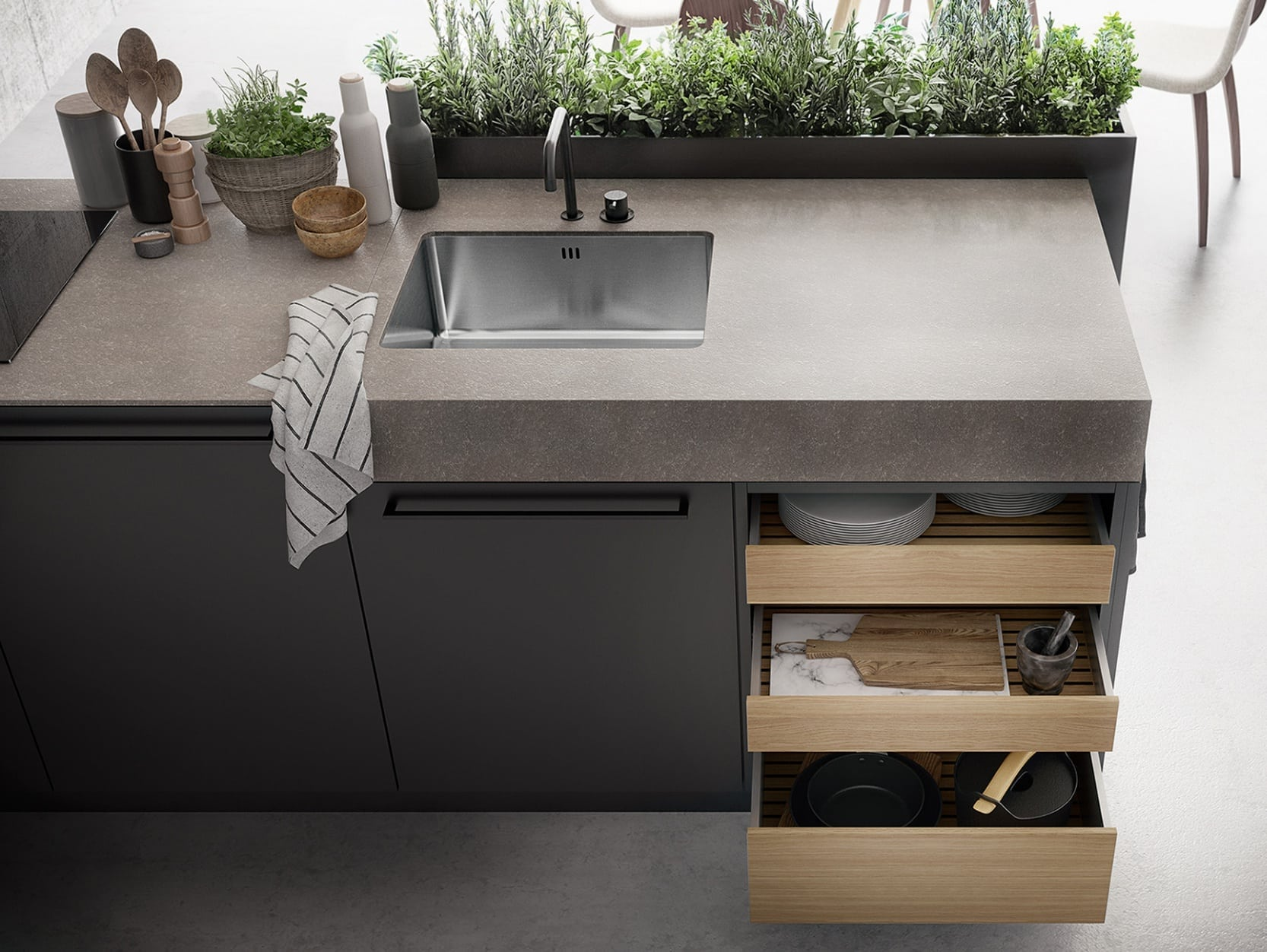 A siematic urban kitchen with wooden drawers sink and stone top
